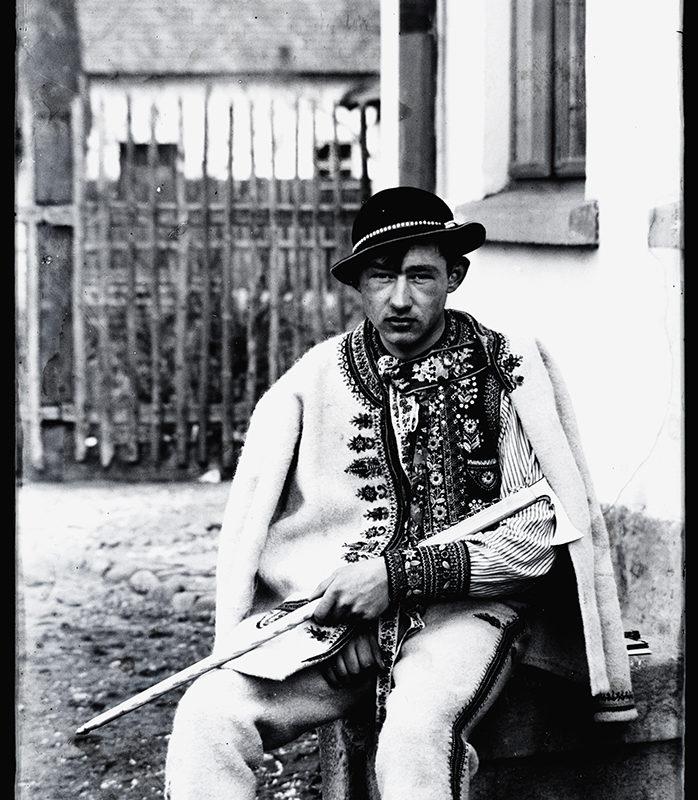 Mężczyzna siedzący na ławce przed domem w ozdobnych spodniach, haftowanej kurtce, kapeluszu ozdobionym muszelkami, trzymający na kolanach ciupagę – strój Górali Szczawnickich