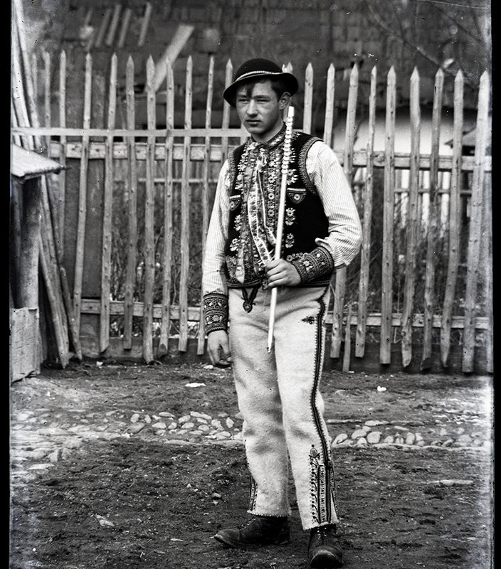 Mężczyzna na podwórzu w ozdobnych spodniach, bogato haftowanej kamizelce i w kapeluszu ozdobionym muszelkami, trzymający ciupagę – strój Górali Szczawnickich
