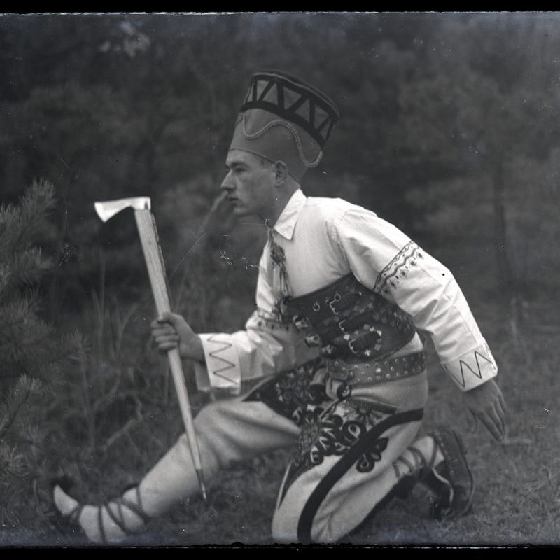 Mieczysław Cholewa w stylizowanym stroju podhalańskim pozuje w figurze z tańca zbójnickiego. Sylwetka widziana jest z profilu, w przysiadzie na prawej nodze i wykroku lewej nogi do przodu, z uniesioną ciupagą w lewej ręce i prawą ręką w pozycji cofniętej.