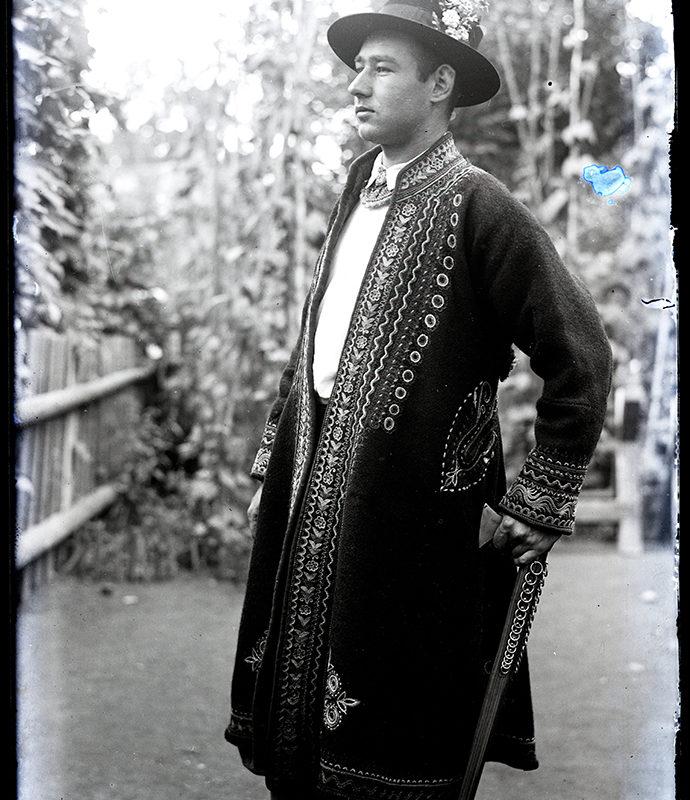 Portret Mieczysława Cholewy, pozującego w stroju Lachów Sądeckich, z widoczną długą haftowaną sukmaną i ciupagą w ręce. Tłem fotografii jest podwórko z fragmentem płotu i przyroda.
