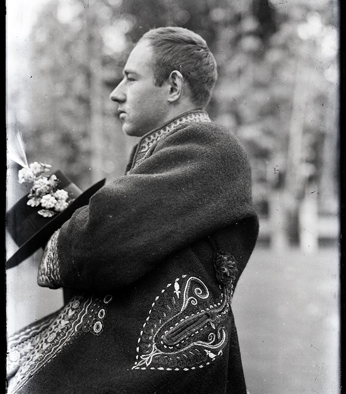 Portret Mieczysława Cholewy ujęty z profilu w planie średnim, na tle przyrody. Mężczyzna ubrany jest w sukmanę Górali Łąckich, w ręku trzyma ozdobiony kwiatami kapelusz.