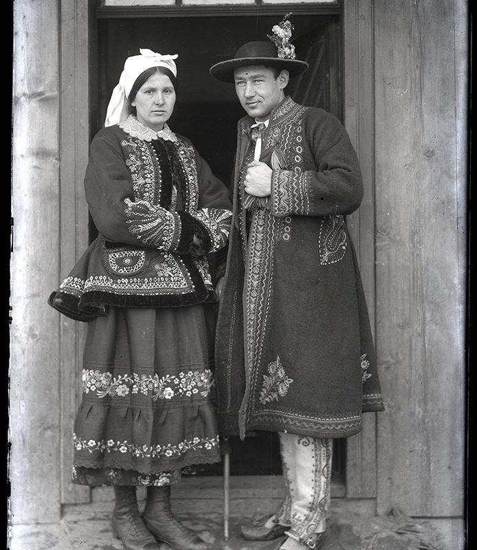 Portret Mieczysława Cholewy i jego żony w strojach Łachów Sądeckich. Para pozuje na progu drewnianego domu, z tyłu widać otwarte drzwi i nadświetle odbijające światło dnia. Kobieta ma na sobie bogato haftowany kaftanik, spódnicę, wysokie buty z cholewami i białą chustę na głowie. Mężczyzna ubrany jest w przyozdobiony kwiatami kapelusz, haftowany długi kaftan, spodnie i kierpce.