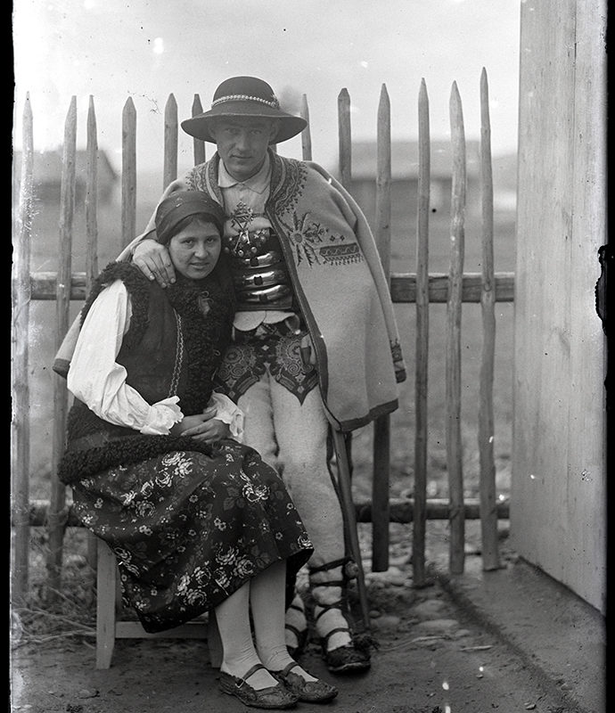 Portret Mieczysława Cholewy z żoną w strojach podhalańskich. Para pozuje na podwórzu przy płocie. Kobieta siedzi na stołku, mężczyzna przytula ją stojąc. Kobieta ubrana jest w skórzaną kamizelkę bez rękawów, chustkę, koszulę i spódnicę, mężczyzna ma na sobie kapelusz, ozdobny pas i spinkę do koszuli, haftowaną narzutę bez rękawów i spodnie oraz koszulę z kołnierzykiem. Oboje patrzą w obiektyw aparatu.
