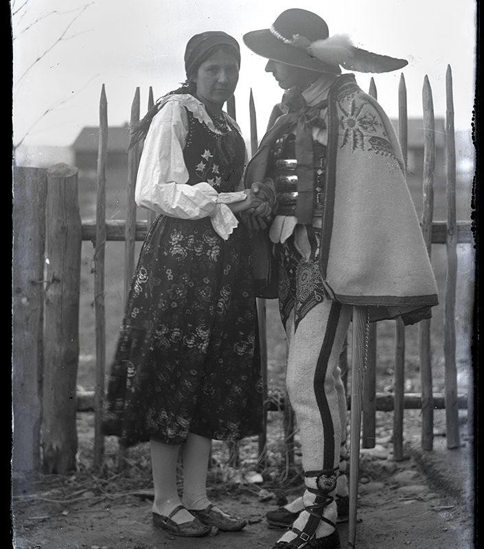 Portret Mieczysława Cholewy z żoną w strojach podhalańskich. Plan pełny na tle płotu i zabudowań gospodarczych. Kobieta patrzy w obiektyw, ma na sobie gorset, koszulę, spódnicę, kierpce i chustkę na głowie. Mężczyzna patrzy na kobietę, ubrany jest w kapelusz z piórem, harfowaną narzutę bez rękawów, szeroki ozdobny pas, haftowane spodnie i kierpce.