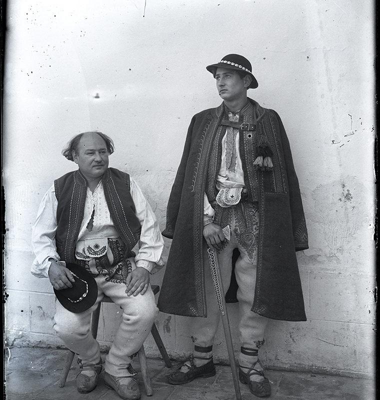 Dwóch mężczyzn ubranych w strój Górali Sądeckich - jeden siedzący na stołku ubrany w ozdobne spodnie, lnianą koszulę, kamizelkę i kierpce, trzymający w ręku kapelusz oraz drugi stojący, ubrany w ozdobne spodnie, lnianą koszulę, kamizelkę oraz ozdobne okrycie wierzchnie w kierpcach i z ciupagą.