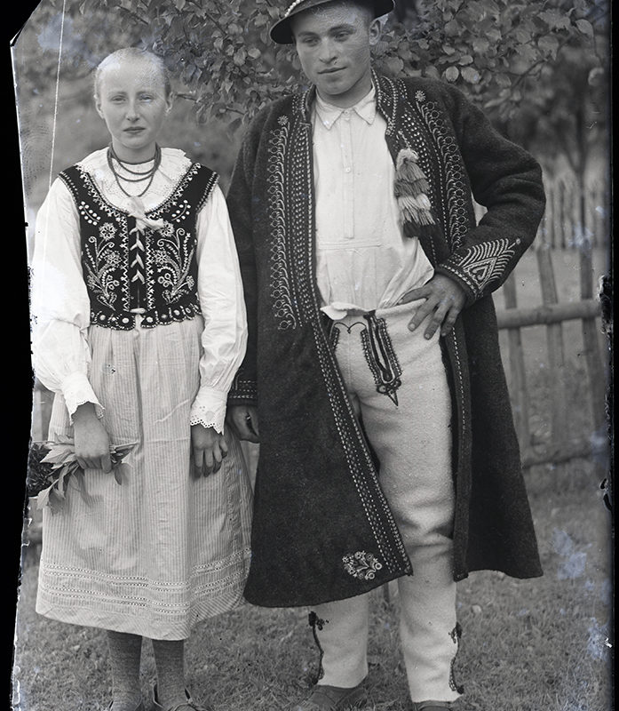 Para w strojach Górali Łąckich, pozująca w pełnym planie na tle sadu i drewnianego płotu. Kobieta ubrana jest w koszulę, spódnicę, haftowany gorset i korale, mężczyzna ma na sobie kapelusz, koszulę, haftowany kaftan i haftowane spodnie.