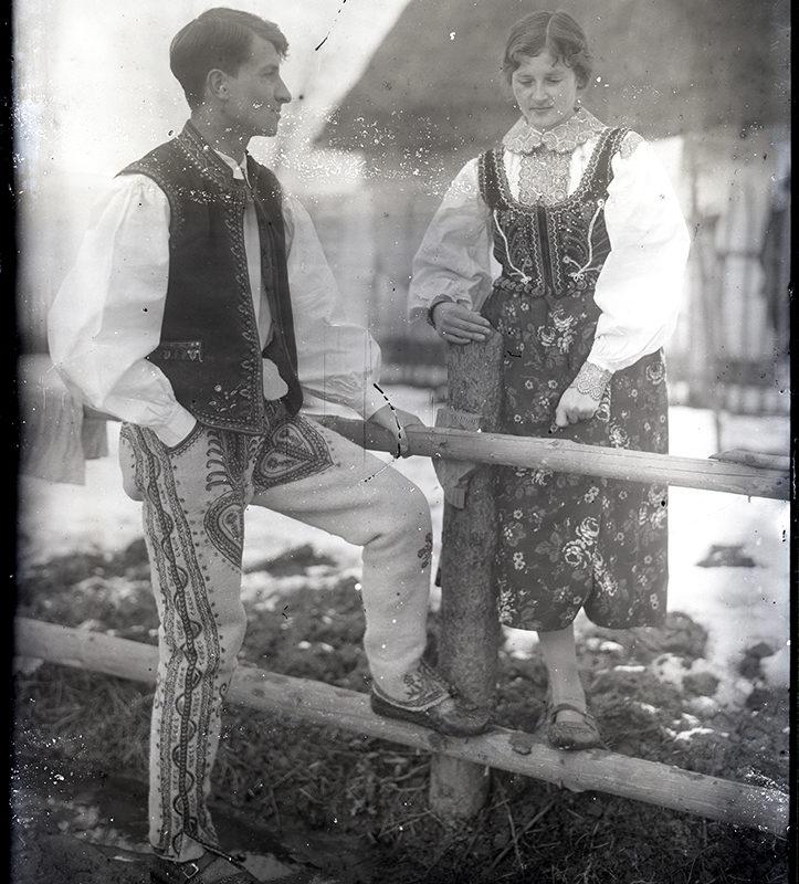 Para w stroju Górali Sądeckich, pozująca przy drewnianym ogrodzeniu, opierając nogi o poprzecznej belce i ręce na konstrukcji płotu. Kobieta ubrana jest w białą koszulę, haftowany gorsecik i kwiecistą spódnicę, mężczyzna ma białą koszulę, haftowaną kamizelkę i spodnie. Oboje noszą kierpce. W tle zabudowania gospodarcze.