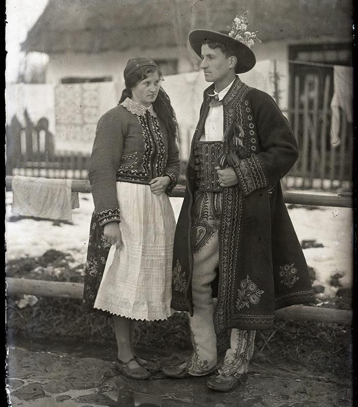 Para w stroju Górali Sądeckich, pozująca na tle zabudowań gospodarczych, widoczny śnieg i błoto w obejściu. Stojąca z lewej strony kobieta ubrana jest w haftowany z przodu i na rękawach kaftanik, spódnicę z białym fartuchem, kierpce i chustkę na głowie. Mężczyzna ma na głowie kapelusz ozdobiony dodatkowo kwiatami, haftowany kaftan, koszulę i ozdobny pas, haftowane spodnie i kierpce.