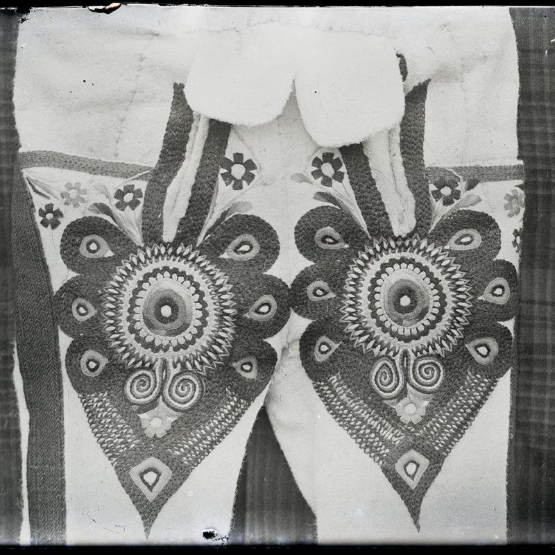 Haftowane parzenice na nogawkach spodni góralskich, wyeksponowane na kraciastej tkaninie.