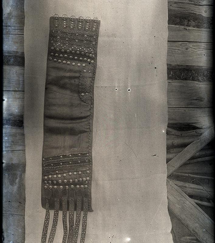 Pas Lachów Sądeckich, wyeksponowany na kawałku białego płótna rozłożonego na deskach. Pas jest szeroki, ozdabiany techniką nitowania i dziurkowania w okolicy zapięcia, na środku bez ozdób.