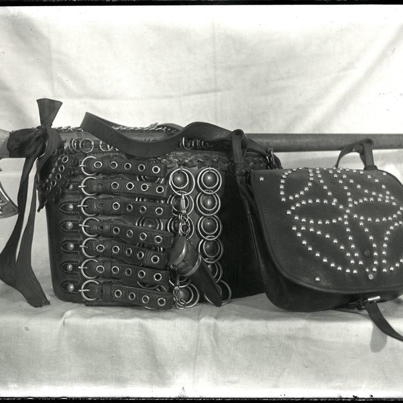 Elementy stroju Górali Łąckich: siekierka z ozdobnym motywem szarotki na ostrzu, szeroki pas skórzany nitowany z okrągłymi sprzączkami, torba z wybijanym ćwiekami rozetowym ornamentem na klapie.