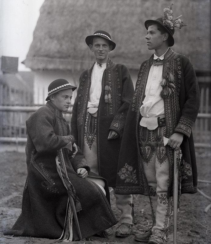 Portret trzech mężczyzn w strojach łąckich na tle zabudowy gospodarczej. Mężczyźni ubrani są w długie haftowane sukmany, kapelusze (jeden z nich ozdobiony kwiatami), haftowane bogato spodnie i białe koszule, w ręku trzymają ciupagi. Dwóch z nich stoi, jeden siedzi.