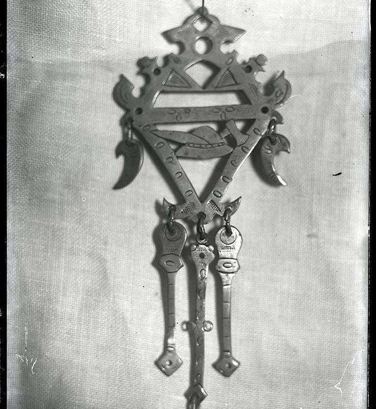 Metalowa spinka do koszuli męskiej, składająca się z romboidalnej ażurowej podstawy zdobionej po bokach z motywem kapelusza i ciupagi w środku oraz dołączonych do niej elementów ruchomych: dwóch zbliżonych kształtem do półksiężyców po bokach oraz trzech podłużnych, zawieszonych u podstawy rombu.