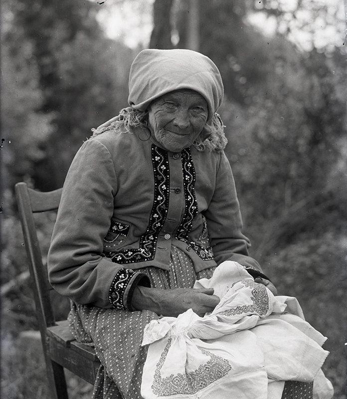 Portret starszej kobiety w stroju Lachów Sądeckich siedzącej na krześle na tle przyrody. Kobieta ma na głowie chustkę, ubrana jest w haftowany z przodu i przy rękawach kaftanik i spódnicę. Na kolanach trzyma białą haftowaną tkaninę.