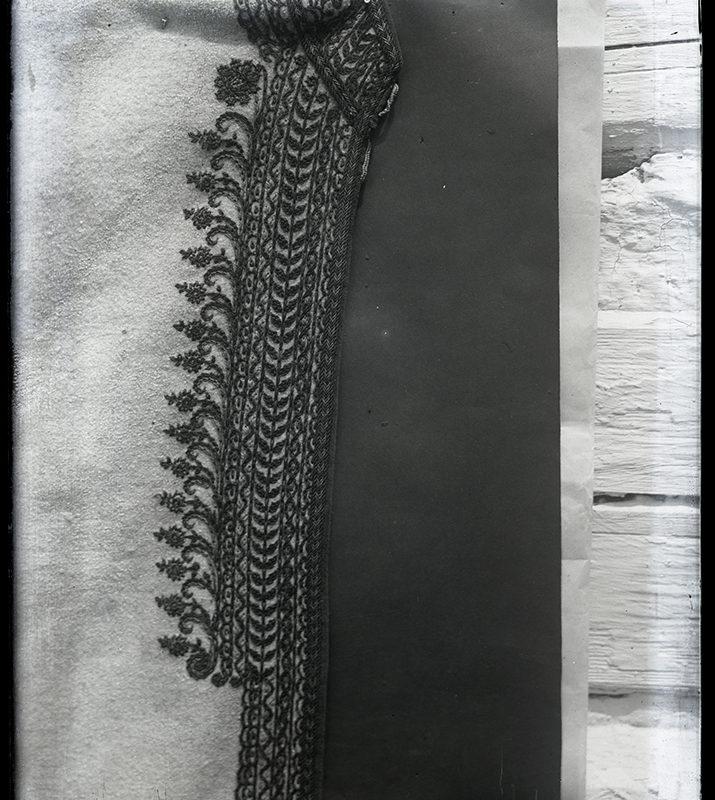 Fragment stroju Górali Łąckich: brzeg białej sukmany haftowany nicią w kontrastowym kolorze w wielorzędowy wzór, wykończony florystycznym ornamentem.