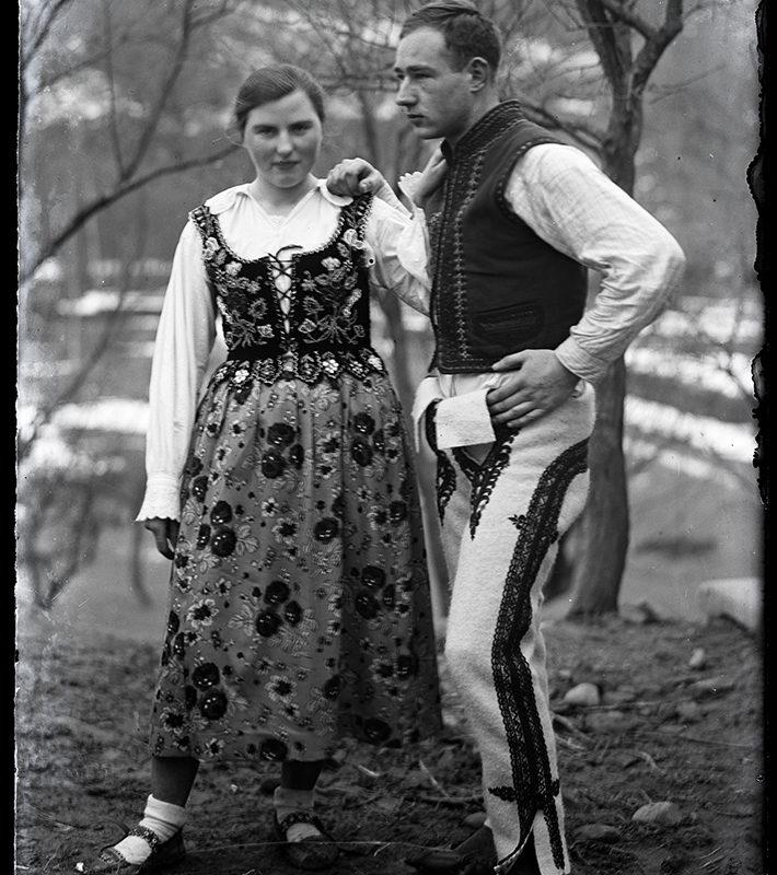 Zdjęcie portretowe pary w stroju z okolic Zarzecza na planie pełnym, na tle natury. Po lewej stronie kobieta w białej koszuli, haftowanym gorsecie i kwiecistej spódnicy i kierpcach, po prawej Mieczysław Cholewa w koszuli, kamizelce i haftowanych spodniach.