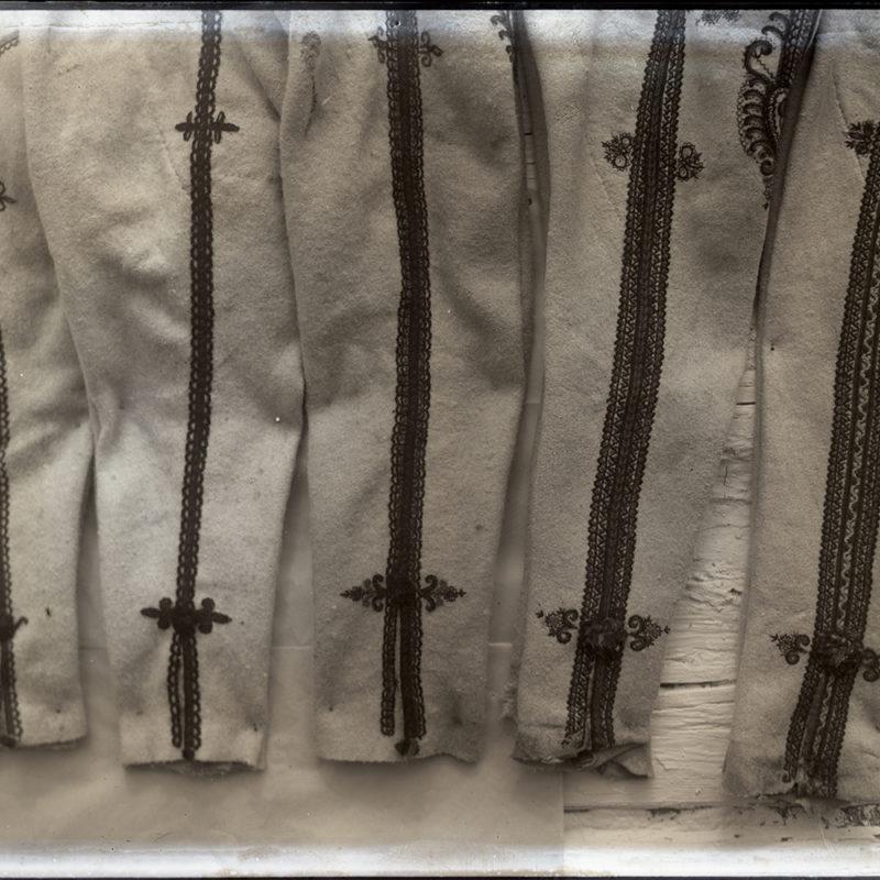 Na zdjęciu widoczne są nogawki męskich spodni (portek) góralskich, haftowane ozdobnie przy lampasach, z fragmentami parzenic w górnej części, wyeksponowane na podstawie z desek.