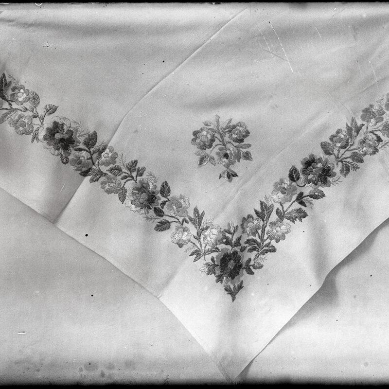 Fragment chusty, kobiecego elementu stroju łąckiego. Widoczny narożnik haftowany dookolnie haftem płaskim z wykorzystaniem ornamentu florystycznego. Raport wzoru umieszczono także w rogu chusty.