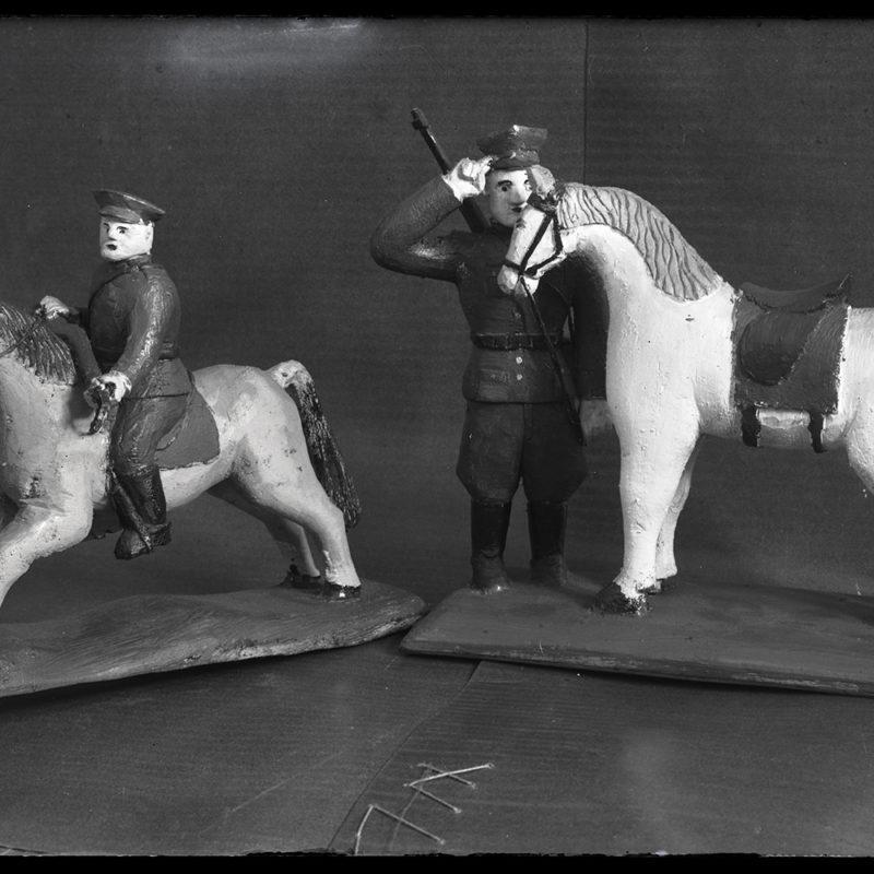 Fotografia przedstawia dwie drewniane figurki koników i żołnierzy na płaskich podstawkach z deseczki. Figurka z lewej strony to żołnierz jadący na koniu, z prawej strony żołnierz stoi przy końskiej głowie, salutując.