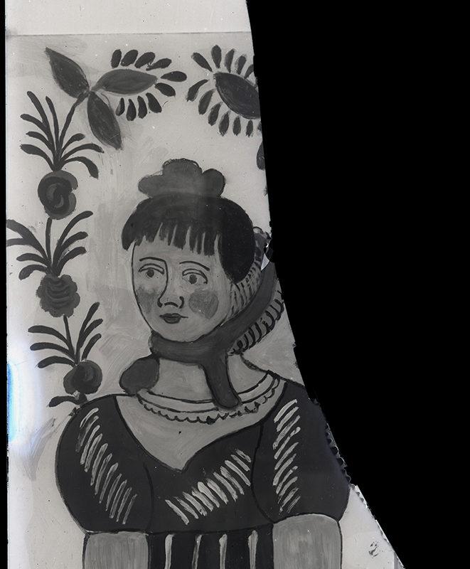 Fragment malowidła na szkle z przedstawieniem Janosikowej Frajerki. Dziewczyna namalowana została w ozdobnej sukience i w kapelusiku na głowie, nad nią widoczny fragment kwiatowego ornamentu. Część zdjęcia zaczerniona, bez szczegółów.