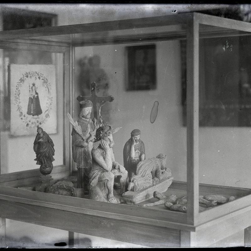 Gablota muzealna z miniaturowymi rzeźbami. Przedstawienia Chrystusa Frasobliwego, Matki Bożej, świętych męczenników. W tle widoczne nieostro wiszące na ścianie muzeum obrazy.