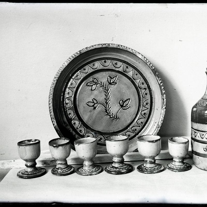 Komplet wyrobów ceramicznych: sześć kieliszków z falistym ornamentem na podstawce, z prawej strony butelka z ornamentem i ozdobnym korkiem, w tle talerz z centralną dekoracją roślinną.