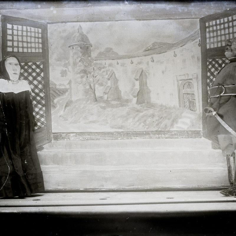 Fragment szopki lalkowej z, na zdjęciu przedstawiony centralnie namalowany widok z okna na miejskie mury z przyporami i okrągłą basztę. Przed okiennicami we wnętrzu stoją po obu stronach okna lalki – kukiełki, jedna z nich przedstawia kobietę w czarnym płaszczu z kapturem i białą kryzą kołnierza, trzymającą w ręku pastorał, druga to stojący bokiem wojskowy w mundurze i z szablą.