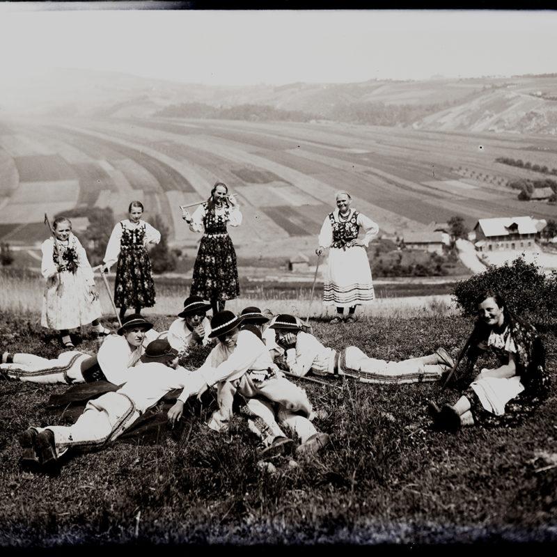 Zespół taneczny Mieczysława Cholewy pozuje na górskiej łące, w tle pola i zarys gór. Na pierwszym planie grupa mężczyzn leży na ziemi w kręgu, stopami na zewnątrz, podparta na rękach, jeden z mężczyzn obraca się ciałem w kierunku obiektywu. Obok nich siedzi kobieta, cztery pozostałe stoją z ciupagami w rękach na drugim planie.