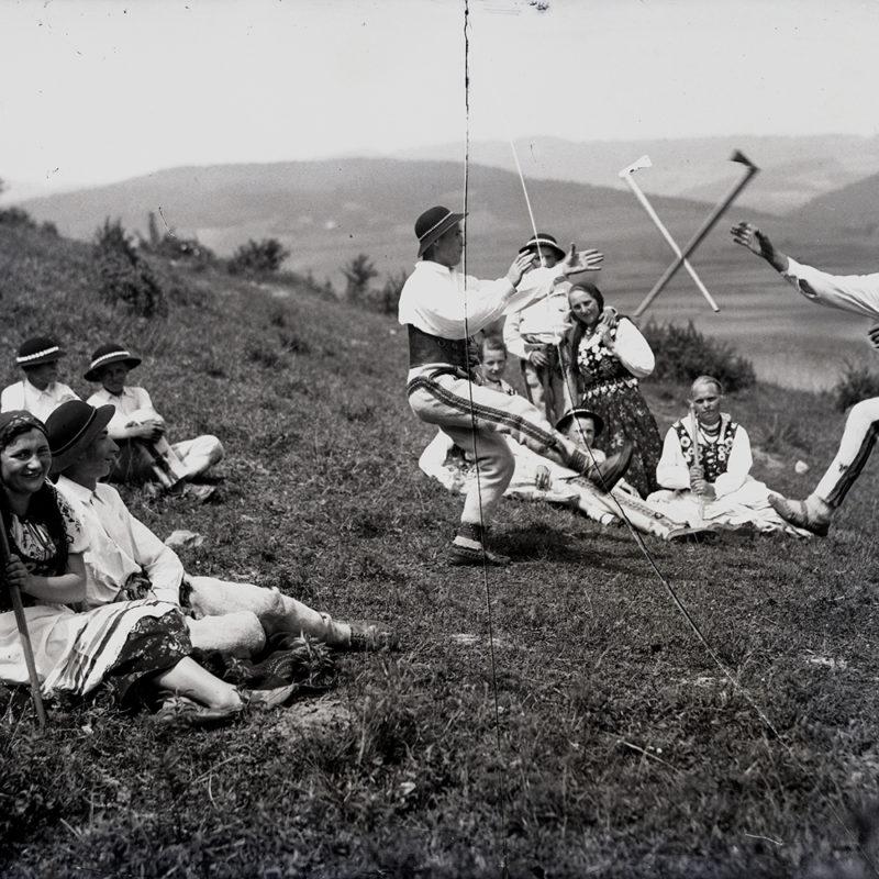 Grupa osób w strojach ludowych upozowana na górskiej łące z widokiem na góry. Kilka osób siedzi na trawie, kobieta na pierwszym planie uśmiecha się i patrzy w obiektyw. Na drugim planie dwóch mężczyzn tańczy taniec zbójnicki, aparat uchwycił chwilę, gdy przerzucane między nimi ciupagi są w powietrzu, jedna noga tancerzy w wymachu, druga ugięta, obie ręce wyciągnięte w kierunku ciupag.