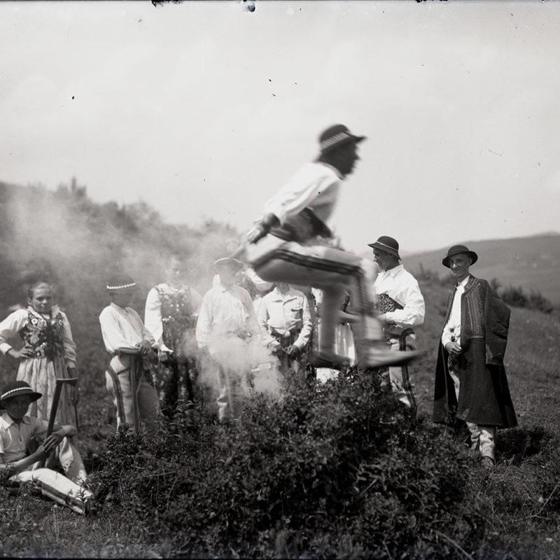 Grupa osób w strojach ludowych sfotografowana na tle przyrody. Jeden z mężczyzn uchwycony w momencie skoku przez ognisko (na zdjęciu widoczny jest dym), co jest elementem tańca zbójnickiego. Reszta osób stoi na drugim planie i przygląda się jego popisowi.