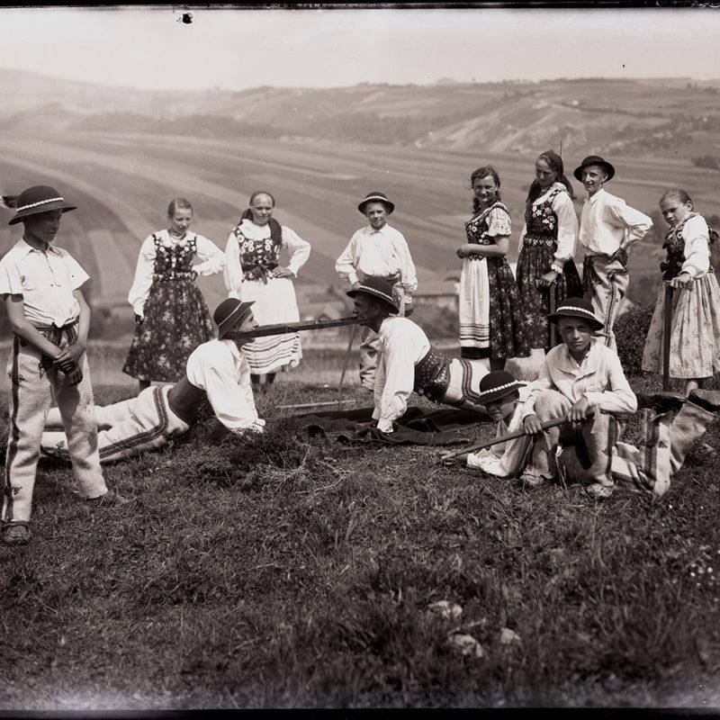 Grupa osób w strojach podhalańskich pozuje na tle górskiego pejzażu. Na pierwszym planie siedzą, leżą i stoją chłopcy. Na drugim dwóch mężczyzn złączonych przewiązanym za szyję skórzanym pasem półleży naprzeciw siebie i, podpierając się na rękach, ciągnąc pas każdy w swoją stronę. W ostatnim rzędzie grupa kobiet i mężczyzn przygląda się scenie zabawy.