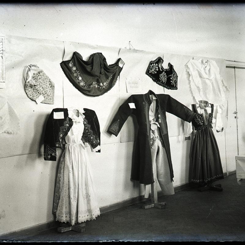 Ekspozycja strojów Laszek sądeckich i męski strój Górali Łąckich. Suknie kobiece białe z haftowanymi kaftanami, męskie okrycie wierzchnie haftowane, spodnie i koszula, obok eksponowane chusty, haftowany gorsecik i koszula