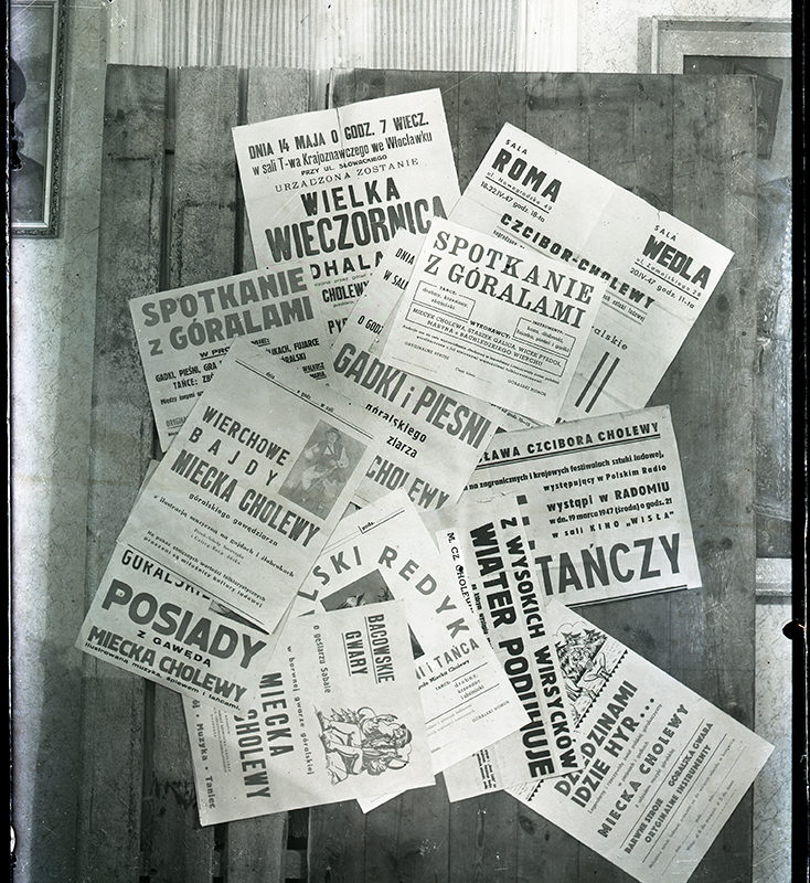 Zbiór plakatów imprez i wydarzeń, organizowanych przez Mieczysława Cholewę, naklejony na fragment drewnianego płotu w fantazyjnym nieuporządkowanym układzie.