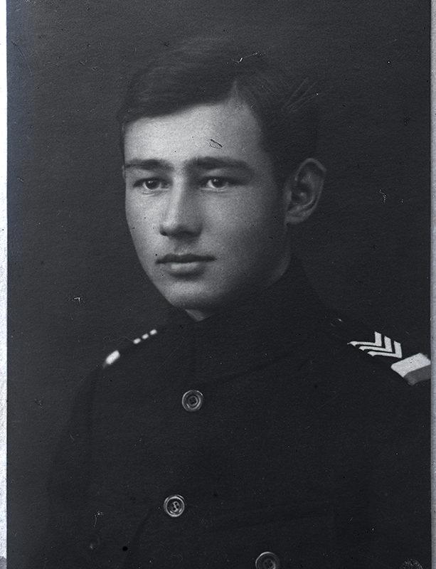 Zdjęcie portretowe Mieczysława Cholewy w półzbliżeniu i w półprofilu, ubranego w mundurek z dystynkcjami i barwami narodowymi na ramieniu.