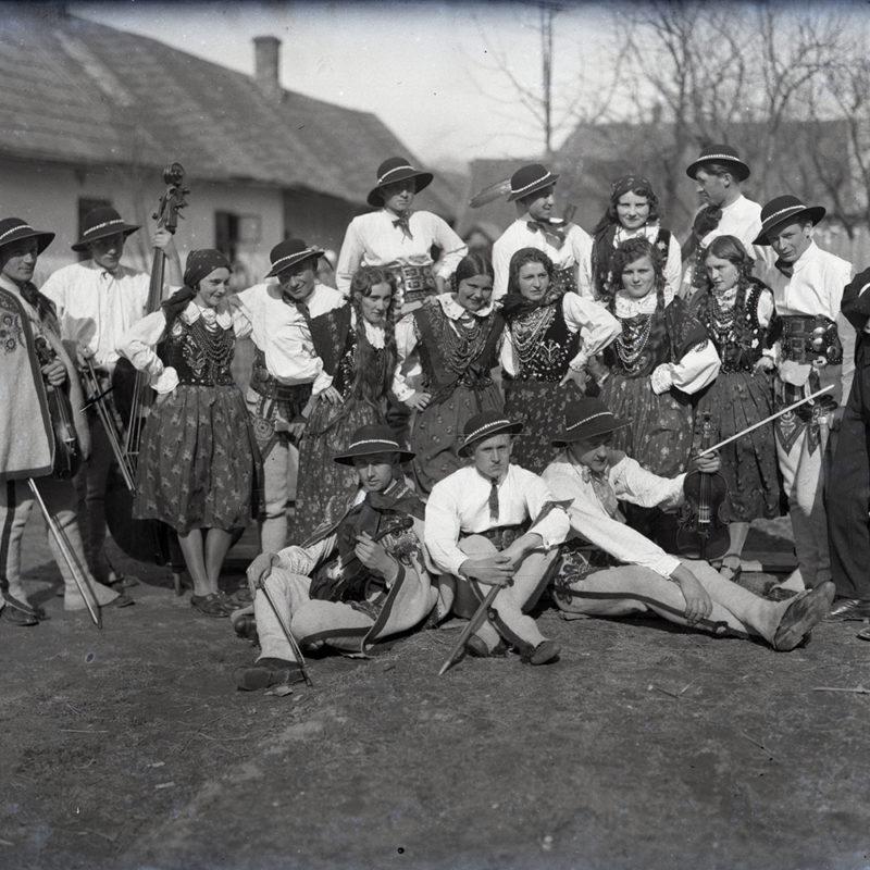 Muzyczny zespół folklorystyczny, pozujący w strojach podhalańskich na tle zabudowań gospodarstwa. Trzech mężczyzn siedzi na pierwszym planie, na kolejnym kobiety prezentują się w tanecznej pozie z rękami na biodrach, trzeci rząd osób stoi. Widoczne instrumenty: skrzypce i basy. Z boku mężczyzna w garniturze patrzy na zespół.