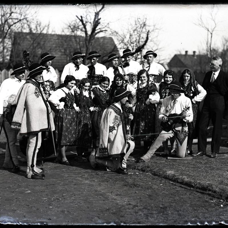 Muzyczny zespół folklorystyczny, pozujący w strojach podhalańskich na tle zabudowań gospodarstwa, sfotografowany z boku. Osoby stoją w trzech rzędach, kobiety w drugim rzędzie w pozie tanecznej z rękami na biodrach, dwóch mężczyzn na pierwszym planie ze skrzypcami w rękach demonstruje w przyklęku instrumenty. Z boku grupy mężczyzna w garniturze, przygląda się swobodnie zespołowi.