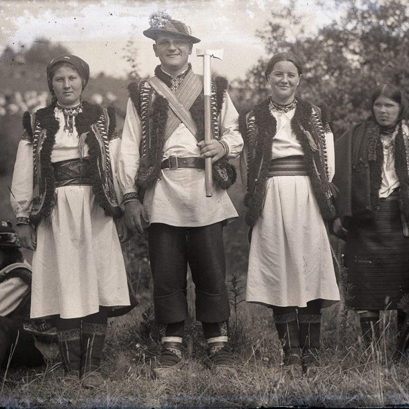 Dwie kobiety i mężczyzna w strojach huculskich, pozujący frontalnie do zdjęcia w plenerze. Na drugim planie kilka osób w strojach ludowych, w tle łąka i drzewa.