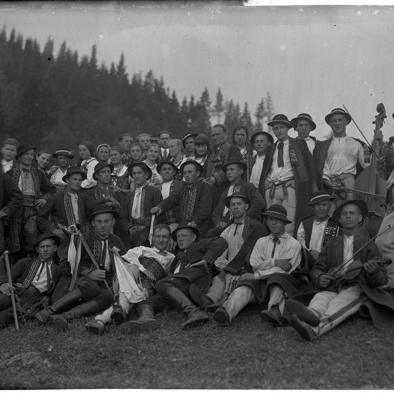 Grupa górali pozująca w strojach sądeckich na tle jodłowego lasu. Większość z nich to mężczyźni, Kilku z nich trzyma instrumenty (basy, skrzypce, klarnet, trąbka). Na pierwszym planie Mieczysław Cholewa, trzeci od lewej strony.