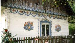 Kolorowe zdjęcie fragmentu zalipiańskiego domu - w centrum zdjęcia znajduje się pomalowane na niebiesko okno. Na białym domu wokół okna wymalowane zostały charakterystyczne dla Zalipia kwiaty. Przed domem skromny, drewniany płotek