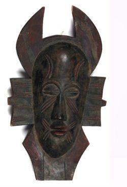 Kolorowe zdjęcie ciemnobrązowej drewnianej maski afrykańskiej Kpelie. Maska przedstawia kobiecą twarz z z nacięciami na czole, policzkach i przy ustach. Od głowy odchodzą płaskie powierzchnie u góry przypominające nieco rogi, po bokach prostokątne płaskie uszy i u dołu coś w rodzaju brody.