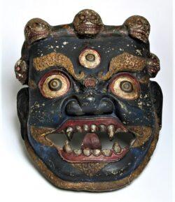 Zdjęcie kolorowe przedstawiające tybetańską maskę w kolorze ciemnogranatowym z wizerunkiem twarzy o wyszczerzonych groźnie kłach. Widoczne dwie wybałuszone i przekrwione gałki oczne oraz trzecia, mniejsza na środku czoła. Nad czołem wizerunek trzech czaszek. Wokół oczu i ust widoczne zdobienia w kolorze złotym.