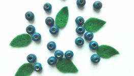Na białym tle rozrzucone koraliki w kształcie małych kulek przypominających jagody. Wśród nich małe listki wycięte z filcu.