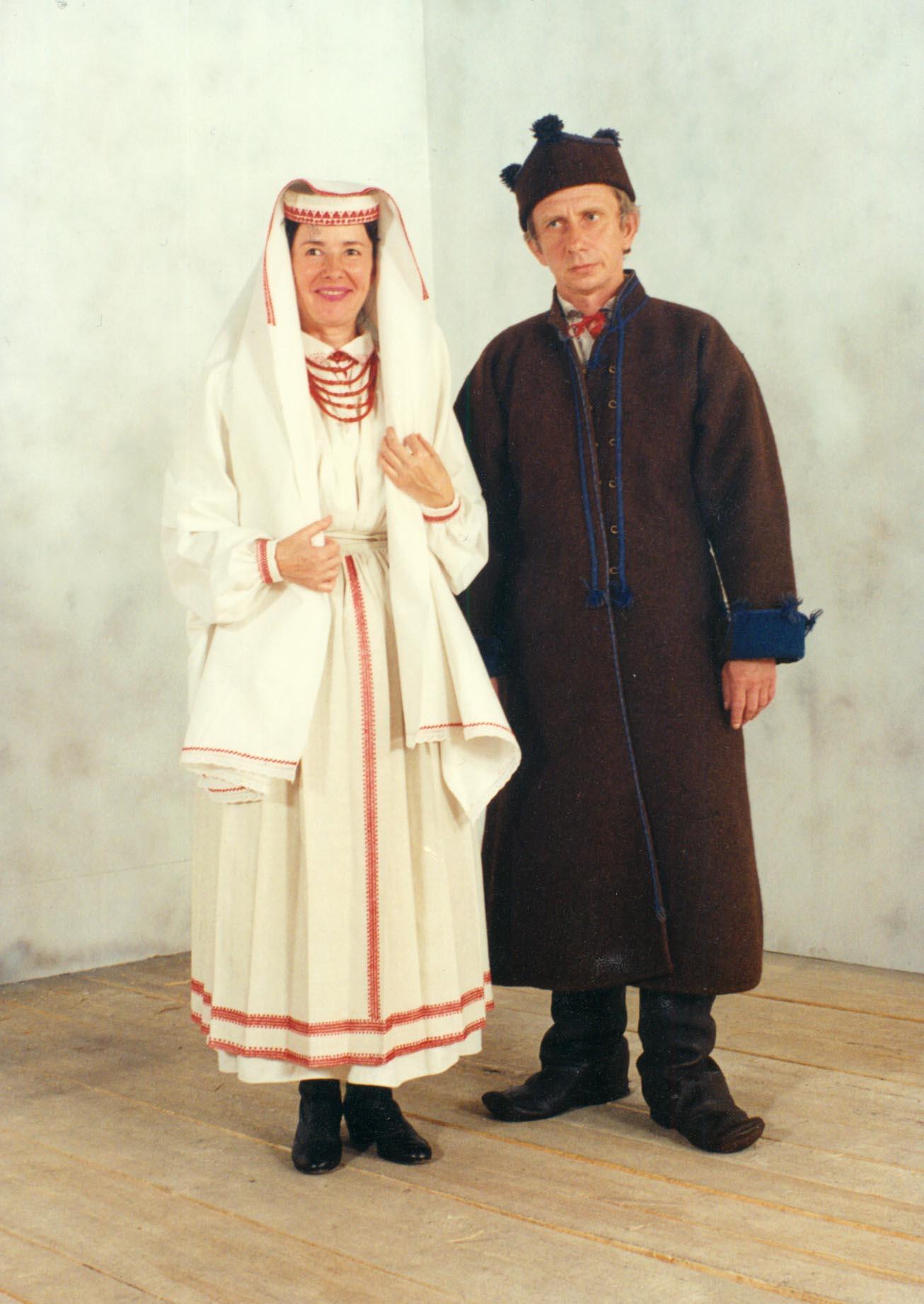 Zdjęcie pary ubranej w tradycyjne stroje biłgorajskie. Kobieta w białym stroju i czepcu z czerwonymi przeszyciami, w czerwonych koralach, na nogach ma czarne obuwie. Męższyzna natomiast ubrany jest w strój w kolorze brązowym z elementami intensywnego granatu, posiada specyficzne okrycie głowy z trzema pomponami oraz obszerne buty. Para stoi na tle pustego pomieszczenia.