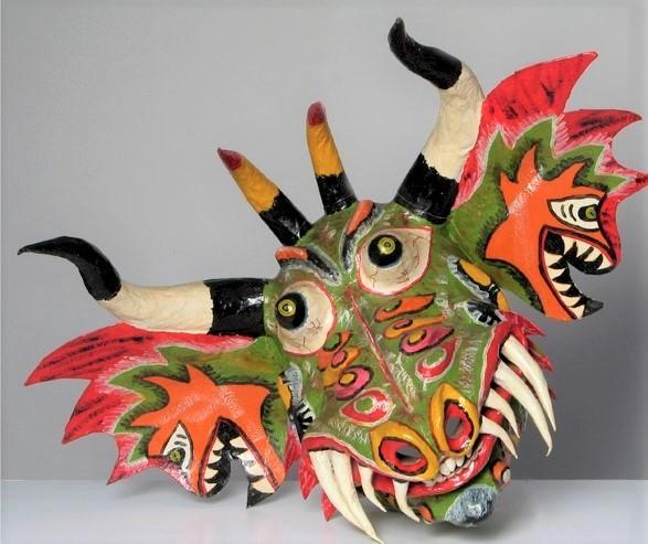 Drewniana maska diabła z Wenezueli. Maska jest bardzo kolorowa, przypomina paszczę smoka - dominuje kolor zielony, pomarańczowy i czerwony. Z paszczy wystają kły, a na czubku głowy widać nieco zakręcone czarno białe rogi. W mocno wystających na boki uszach widać dodatkowe diabełki z rozwartymi paszczami.