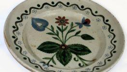 Ceramiczny talerz tradycyjnie zdobiony: po środku talerza malowane kwiaty z liśćmi, zaś na boku talerza falisty wzorek z kropkami.