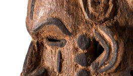 Drewniana, rzeźbiona maska prezentowana z profilu i ukazująca twarz człowieka. Wypukłe elementy twarzy takie jak noc, usta, brwi czy uszy zostały podkreślone czarnym kolorem. Postać z maski nie uśmiecha się.