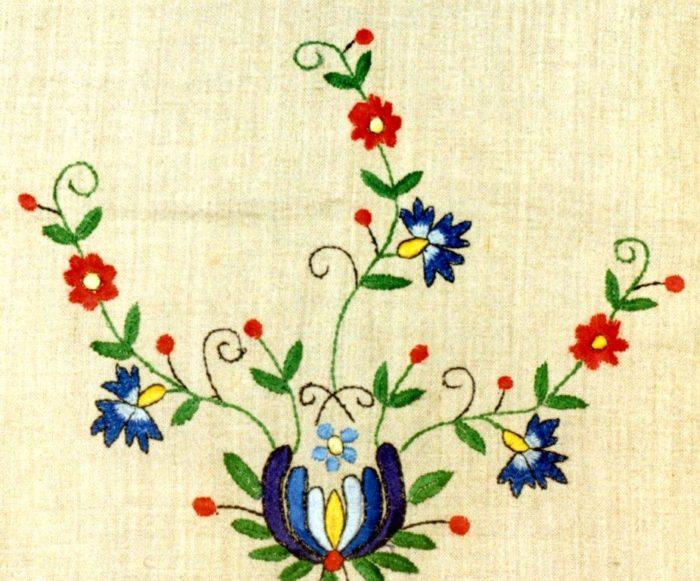 Kolorowy haft kaszubski z rozgałęziającymi się kwiatami.