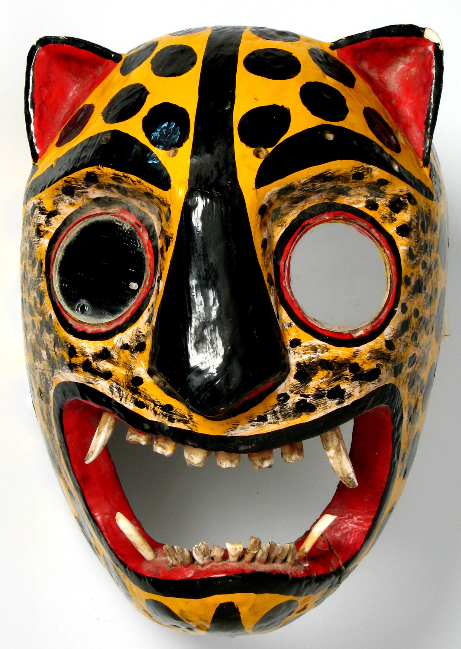 Kolorowa, drewniana maska jaguara z szeroko otwartą paszczą, naturalnymi w niej zębami i lusterkami zamiast oczu.