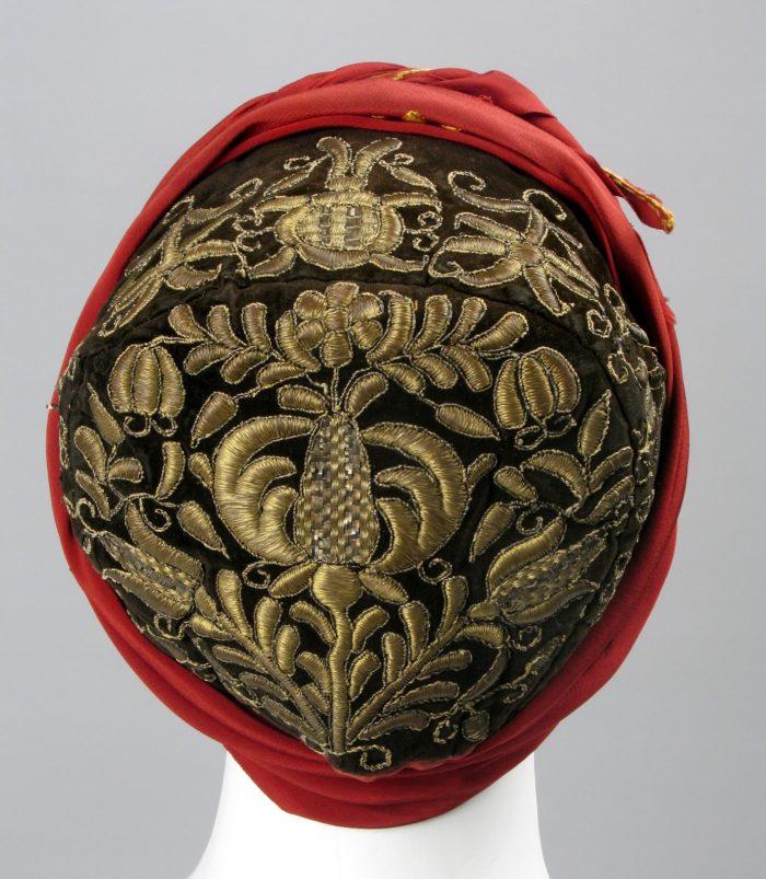 Manekin z nałożonym czepcem kaszubskim wyszytym w ornament złotą nicią.