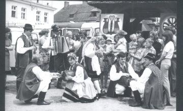 Czarno-białe zdjęcie przedstawiające śpiewaków ludowych i uczestników Festiwalu Kapel Ludowych w Kazimierzu w 1972 roku.